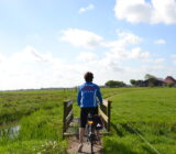 Waddenzee and Friesland staff Sandra cycling through polder landscape